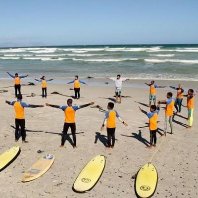 Projects Abroad volunteers teach surfing in South Africa through warm up exercises.